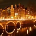 Amsterdam de grachten avonds verlicht.